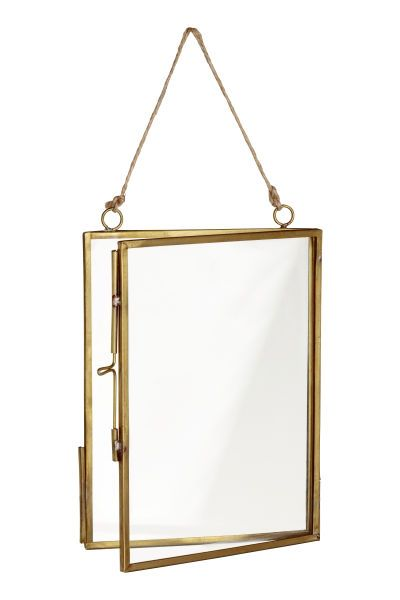 Gold-colored. Frame in metal and clear glass with a sliding latch at one side. Two grommets with a cord for hanging. Screws not included. Fits pictures up