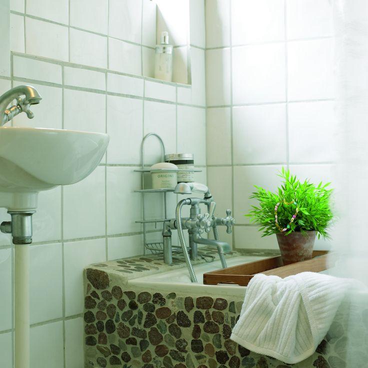 Gulv og badekar er beklædt med smukke flade sten. Badeforhænget er et blondegardin i nylon fra Ikea med et gennemsigtigt plastikforhæng bagved.