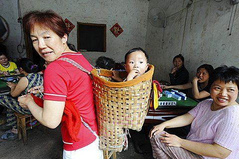 Mother carrying traditional baby carrier made with bamboo in a local teahouse where other women playing Mahjong, Lizhuang Ancient Town, Sichuan Province, China