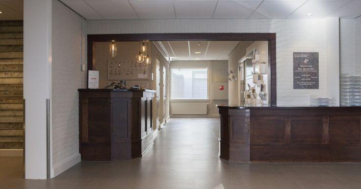 Hotel lobby inrichting. Dit ontwerp is een combinatie van oud en nieuw. De open ruimte maakt dat de houten balie nog beter naar voren komt.