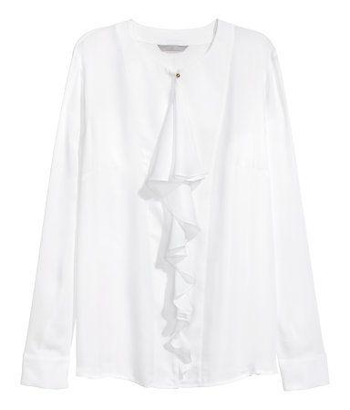 Hvit. En bluse i vevd kvalitet med volang foran. Blusen har metallknapper i halsringningen. Lange ermer med mansjett og knapp.