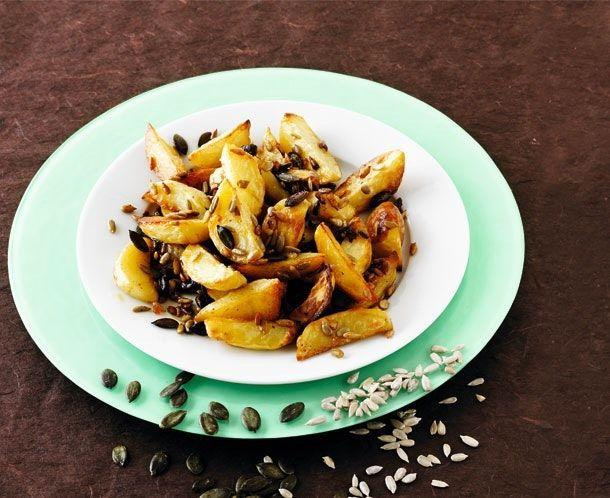 Opskrift på sprøde, ovnbagte kartofler der sammen med græskar- og solsikkekerner står godt til frikadeller, koteletter, andebryst og andet kød fra panden, men de behøver faktisk ikke noget tilbehør.