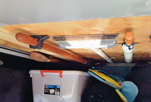 Monte de limpieza y otros artículos largos hasta el techo con los soportes.