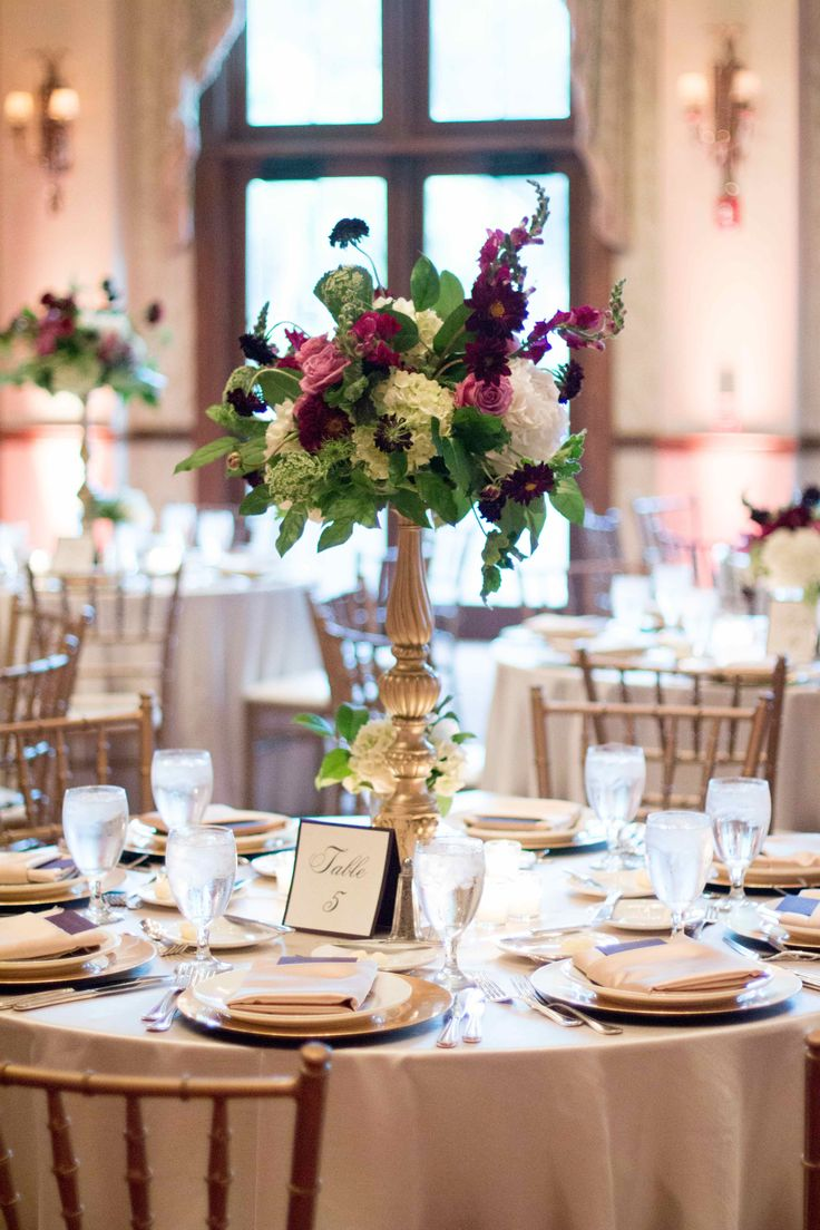 gold in the details of this ballroom reception include gold chiavari chairs, pale gold linens, gold chargers and an ornate gold pedestal for the lush arrangement of purple roses, white hydrangea, burgundy snapdragons, queen anne's lace, burgundy scabiosa and lemon leaf.