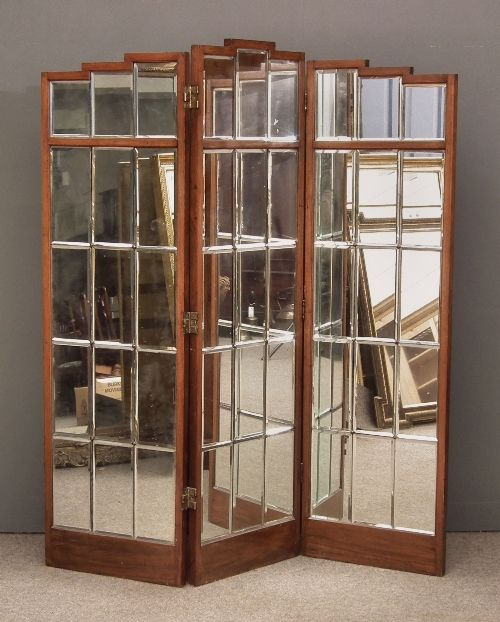 An early 20th Century mahogany framed three fold draught screen of Art Deco design inset with bevelled mirror panels
