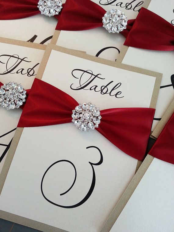 on Etsy. Seems pricey for table numbers so I am making my own. Found rhinestone buckles on Lozs Loot. 25 of them, and they came in about 10 days. Quality is really good. Will incorporate the font from our invitations and print on white card stock, will have black card stock backing and red ribbon.