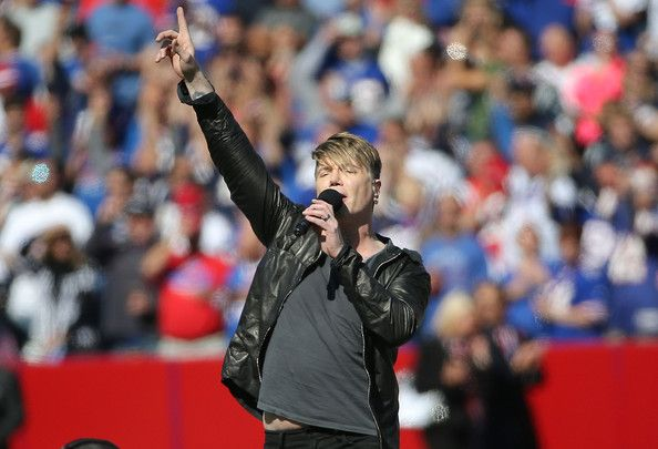 John Rzeznik Photos Photos - Recording artist John Rzeznik sings the national anthem before the first half of the football game between the Buffalo Bills and the New England Patriots at Ralph Wilson Stadium on October 12, 2014 in Orchard Park, New York. - New England Patriots v Buffalo Bills