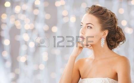 kobieta biżuteria: ludzie, wakacje, ślub, biżuteria i luksusowe koncepcji - piękne kobiety na sobie błyszczące diamentowe kolczyki na światłach tle Zdjęcie Seryjne