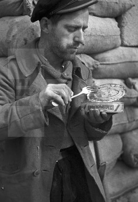 """Spain - 1937. - GC - ZONA REPUBLICANA: MADRID, MARZO DE 1937.- Un combatiente de la 21ª brigada mixta come cangrejo en una lata rusa, proviniente de la empresa """"Dalgosrybtrest"""" (Empresa Estatal Pesquera del Este), en una fortificación de su unidad en el frente de Usera"""