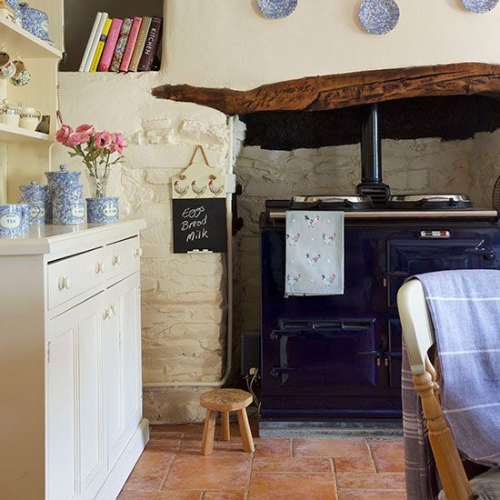 Small kitchen with neutral walls, terracotta florring, neutral dresser and navy Aga
