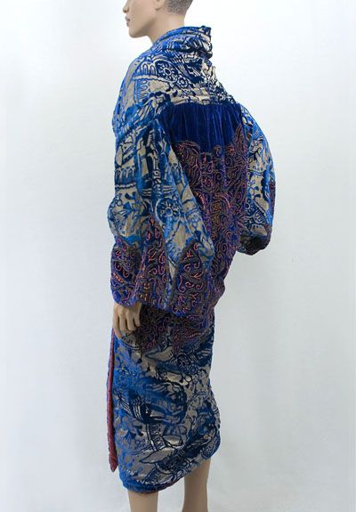 "Opera coat, c.1922 ""The coat is fashioned from cobalt blue devoré velvet, cut to a ground of bronzed gold metallic lamé. The upper back and sleeve borders are of solid silk velvet elaborately embroidered with a Persian pattern of bronze metallic cord and small, coral colored beads. The bodice front sections of the coat are self lined with devoré velvet; the rest of the coat is lined with rose colored silk velvet."""