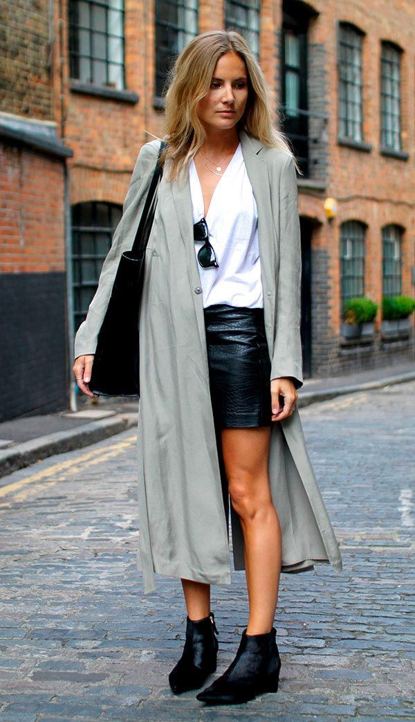 Street style look com saia preta couro, maxi cardigan e camisa decotada.