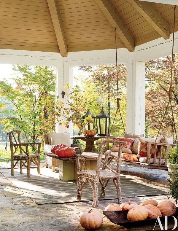 On the porch, a pair of custom-made rustic log chairs from Bennett Galleries | archdigest.com