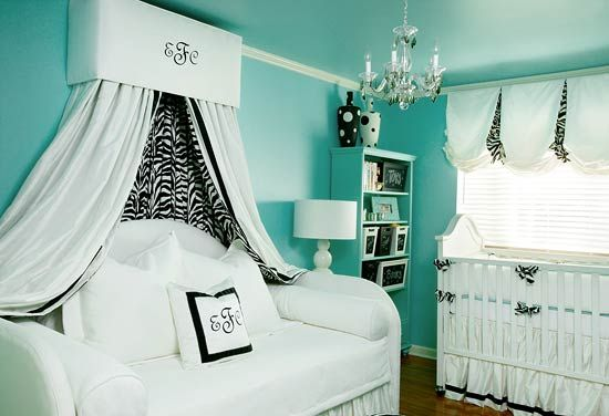 Vibrant turquoise makes this nursery stand out above the rest. Black-and-white zebra stripes tame the wild hue without taking away from its energy. White upholstery lends clean and comfortable lines in the crib and the daybed's canopy. The fluffy daybed is perfect for nursing and napping, while allowing this room to be effortlessly adapted for an older child's room in the future.