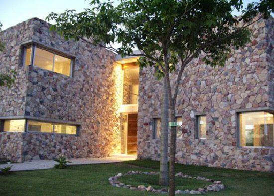 Fachada de casa revestida en piedra y madera:
