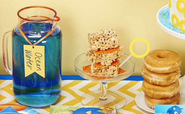 """In need of some themed snack ideas for your little one's Sonic the Hedgehog party? Every little gamer recognizes the importance of golden rings, so we highly recommend incorporating them into as many party treats as possible! Glazed doughnuts, Cheerio snacks and even ring-shaped gummy candies will sure to please your guests. Serve up sweet """"ocean water"""" by whipping up some bright blue fruit punch."""