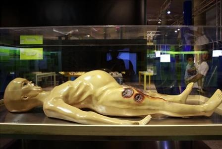Después dicen que no son de verdad | Un hombre carga a su hijo en una sala de modelos de exposición de extraterrestres en Beijing, China.