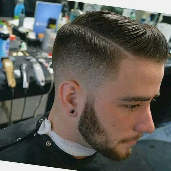 Mid to high skin fade with classic pompadour, hard part, and beard.                                                                                                                                                     More