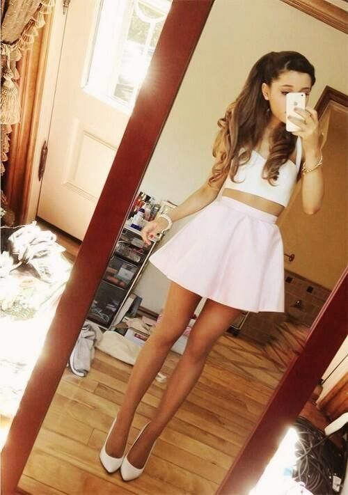 02ecd1d8190 Ariana Grande looking cute in her pale pink mini skirt, white crop top and  high heels while she's taking a mirror selfie.