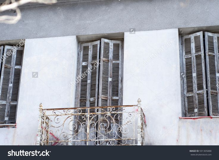 classic building private balcony with rusty design in the front rails and wooden window half open