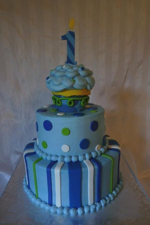 1st Birthday Cupcake - Boy - First birthday cake to match party invites/decorations.  Buttercream icing with fondant accents.  Large cupcake wrapper is molded chocolate.
