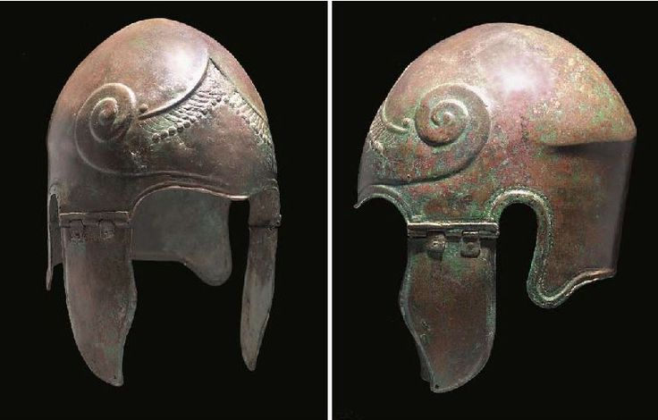 Chalcidian helmet circa 5th-early 4th centuiry B.C. With shallow curve at the brow, the central inverted 'v'-shaped contour with faint traces of a palmette, stylized curled hair below which forms the body of a chased long snouted sea monster with bared serrated teeth and lolling tongue, single and double rows of punched arcs around the helmet edge, the pair of hinged cusped cheekpieces with pierced hole in the lower corner, 29.8 cm high. Private collection, from Christie's auction