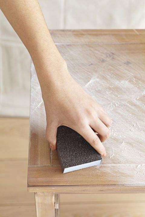 Sand in a circular motion with medium-grit paper to remove any existing paint or stain and (even for raw wood) smooth out the surface. (Do this over a floor covered with newsprint.) Sweep off dust and wipe with a clean, damp cloth.