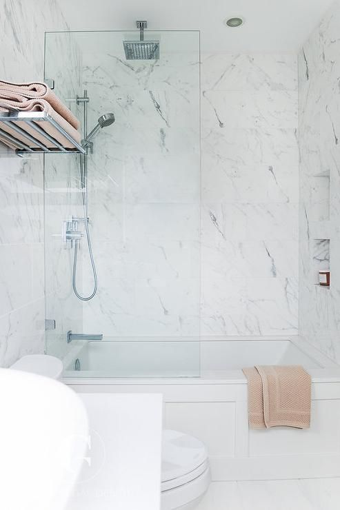 A polished nickel towel rack is mounted to a marble clad wall above a toilet positioned beside a drop in wainscoted tub fitted with with a glass partition and marble wall tiles surrounding tiled niches fixed facing a polished nickel exposed plumbing shower kit paired with a rain shower head.