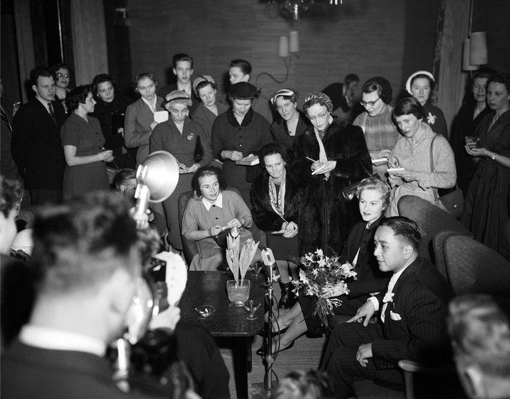 """Hotelli Vaakuna (nyk. Originla Sokos Hotel Vaakuna, Helsinki 22.1.1955. Armi Kuusela ja Gil Hilario lehdistön haastateltavana. """"Kun Armi palasi kotiin Kaliforniasta Miss Universum -kisojen jälkeen, hän asettui asumaan Helsingin hienoimpaan hotelliin, vain muutama kuukausi aiemmin avattuun Vaakunaan."""" Lähde: Sokos-Vaakuna, Maamerkki Helsingin sydämessä, Pälvi & Kimmo Salo"""