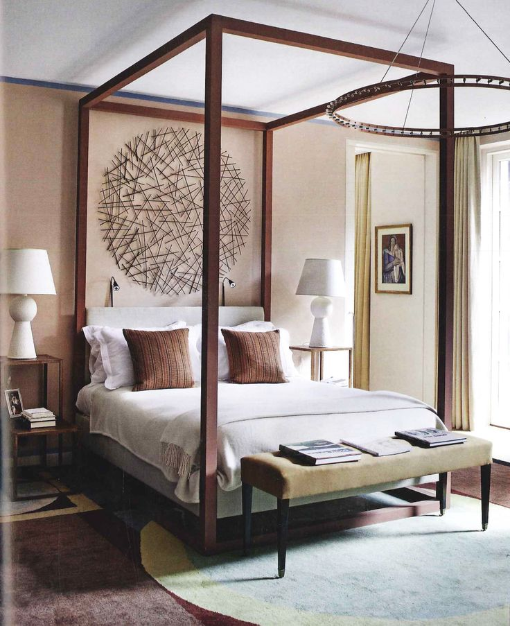 A gigantic circular sculpture by Lizzie Farey, hangs behind a modern four-poster  bed.