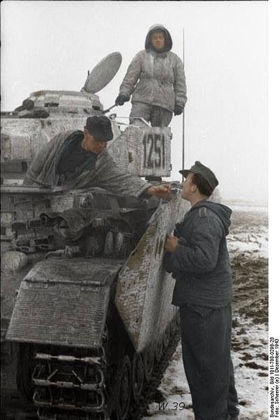 German tank crewman working on a Panzer IV. He is giving his comrade's cigarette a light in this pic....