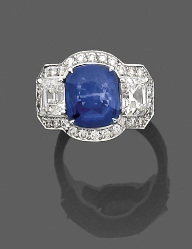 Bague en or gris, ornée au centre d'un saphir coussin épaulé de deux diamants taille émeraude, entouré de