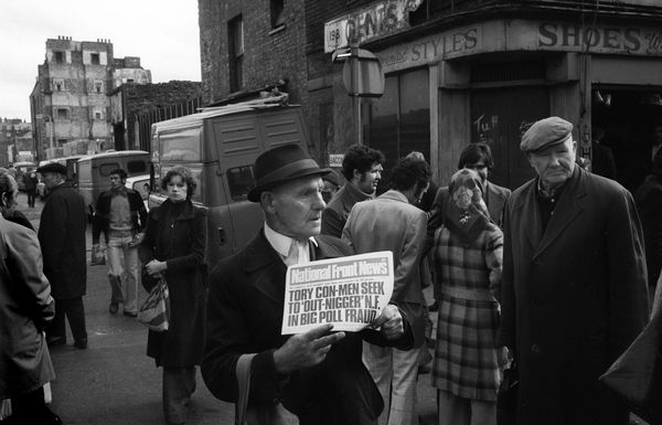 National Front supporter selling National Front News north end of Brick Lane, east London. 1970s. Photographer: Homer Sykes. An extraordinary time capsule of a photograph.