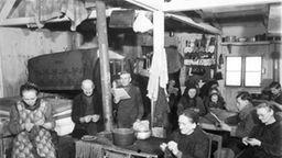 Alltag in einem Gemeinschaftsraum im Flüchtlingslager 'Schlotwiese' in Stuttgart-Zuffenhausen | Bildquelle: Haus der Geschichte Baden- Württemberg, Sammlung Weishaupt