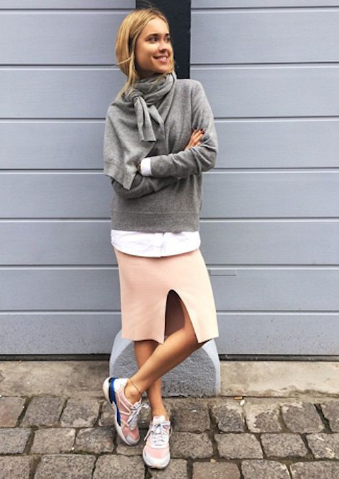 Fashion blogger Pernille Teisbaek wears a gray sweater, an additional sweater wrapped around her neck as a scarf, a slit skirt and pink sneakers