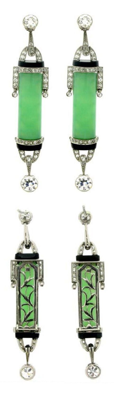 A pair of Art Deco platinum, jade, onyx and diamond earrings. Each vertically set with a central barrel shaped green jade, mounted to top and bottom with borders and stirrup shaped forms flanking horizontal bands of onyx and set with eighty round eight cut diamonds, and each with a round old cut diamond set to top and bottom, the back of the uppermost diamond mounted with post fittings.