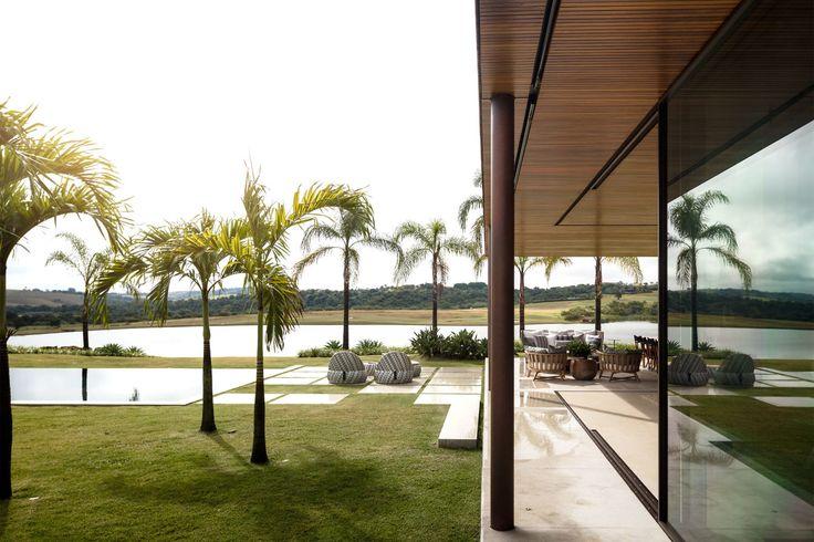 Os vários módulos desta casa, distribuídos no amplo terreno de frente para o mar em Paraty, comunicam-se por passarelas de madeira sobre espelhos d'água.