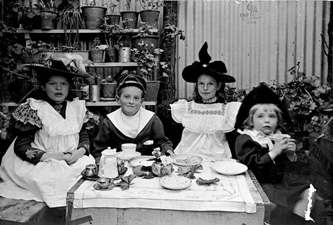 Norwood, South Australia, circa 1897      Four children having a tea party. All wear hats and the two girls wear pinafores. There are shelves of pot plants behind them.