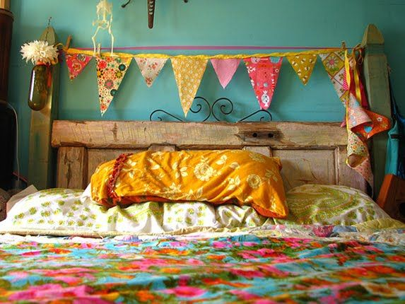 Pretty little kitsch bedroom - cute bunting,  fun floral linen, turquoise wall & upcycled bottle come vase.