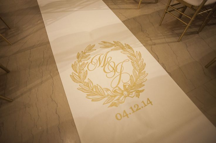 Tennessee Titans player Jason McCourty's custom aisle runner by The Original Runner Company featured a golden crest monogram and the couple's wedding date. #aislerunner #monogram Photography: McLellan Style. Read More: http://www.insideweddings.com/weddings/nfl-tennessee-titans-players-gold-white-wedding-in-nashville-tn/652/