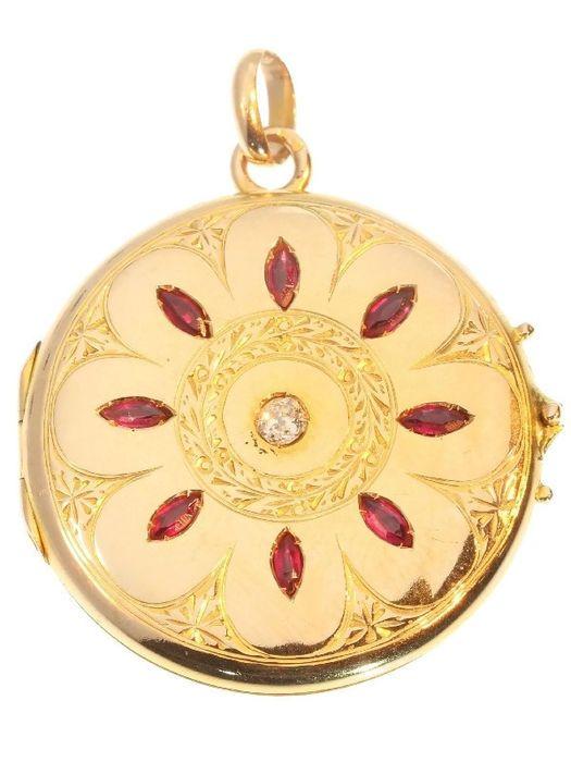 Gouden medaillonhanger met rode stenen en oude briljant geslepen diamanten  Soort juweel: hangerVoorwaarde: In redelijk goede staat met name gezien de leeftijd van de parel. (sommige deuken in de rug - zie foto's)Land van herkomst: Rusland (?) Zie opmerkingen met kenmerkenEra: ca. 1914Materiaal: 14K rood goud (toetssteen getest)Diamanten: Één old mine brilliant cut diamant (ook wel bolshevic genoemd) met een geschat gewicht van  010 ct. (kleur en helderheid: G/H ik).Alle diamant gewichten…