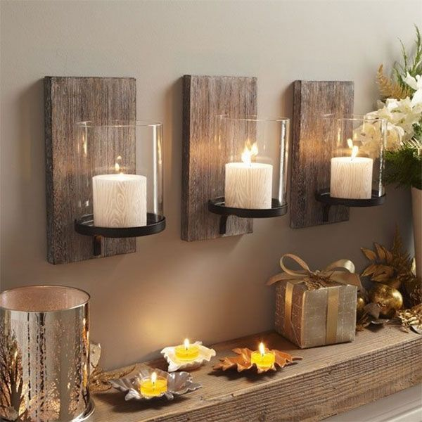Con algunos listones de madera oscura puedes crear lindos porta-velas para pared.