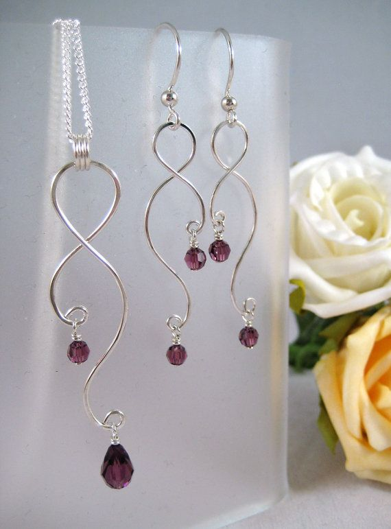 Curving silver wire and crystal earrings and pendant set