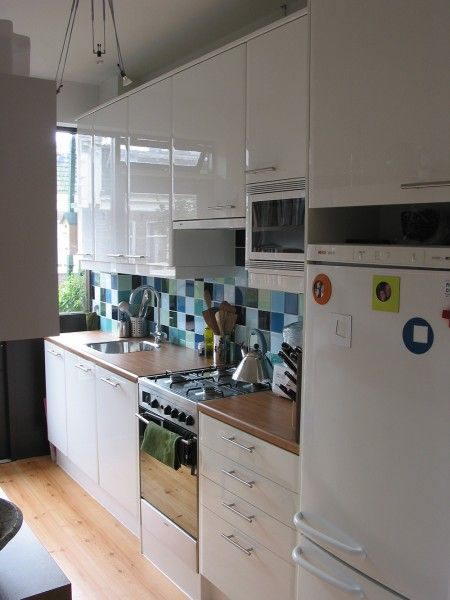 Amsterdam, feature splashback, green & blue splashback, tiled splashback, white kitchen suited for modern apartment living.