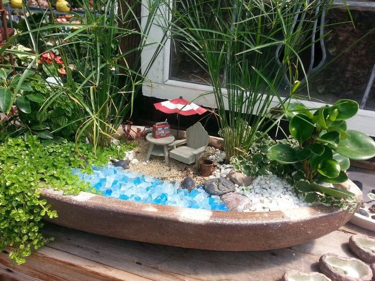 Lakeside Fairy Garden www.teeliesfairygarden.com What I love about this is it is a great garden to start with or have it on your outside tables. I see they are ready for beach fairies and you know they will love the fairy tunes from that radio. #fairylakeside