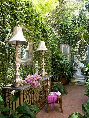 Love this small courtyard. I would love to have this in my backyard! The statue and table add so much to this small garden.