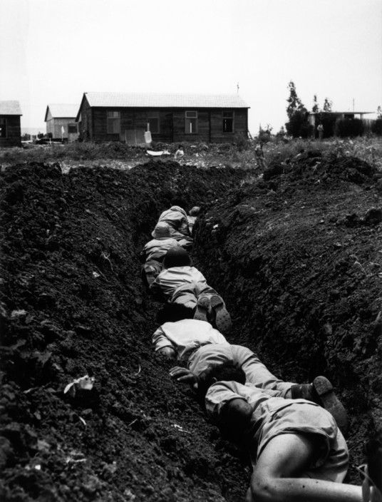 """The """"central front"""". Members of a Kibbutz hiding in a trench during an Arab air-raid. May-June, 1948. © Robert Capa"""