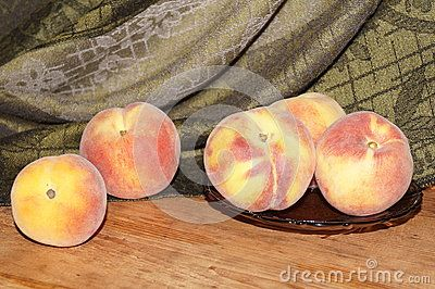Fresh peaches on wooden and green background