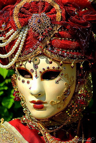 A Venetian mask studded with jewels and topped by a magnificent turban.