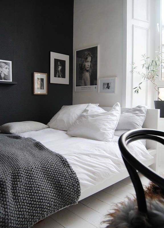 Czarna ściana skontrastowana z białym łóżkiem czy sztukateriami prezentuje się bardzo elegancko. A do tego dodaje wnętrzu głębi. W wystroju postawiono na proste dekoracje – czarno-białe fotografie i piękną fakturę dzierganej narzuty.